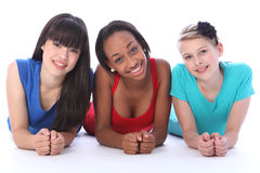 Schwarze weiße und asiatische Freundinnen, die auf Fußboden liegen Stockbild