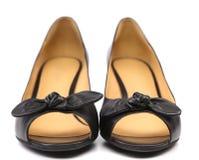 Schwarze weibliche Schuhe mit einem Bogen. Stockfotografie