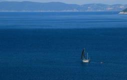 Schwarze Yacht mit schwarzen Verkäufen im blauen Meer Stockbild