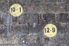 Schwarze Zahlen in einem gelben Kreis gemalt auf dunkler Maurerarbeitwand im Freien Lizenzfreie Stockfotos
