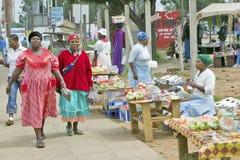 Schwarze Zulu- Frauen in hell farbigen roten Kleidern gehen hinter Erzeugnisverkäufer im Zulu- Dorf im Zululand, Südafrika Lizenzfreies Stockbild
