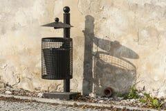 Schwarzer Abfalleimer nahe der Wand Lizenzfreie Stockbilder