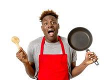 Schwarzer afroer-amerikanisch Mannausgangskoch im Chefschutzblech die Wanne und Löffel kochend verloren und überbelastet lizenzfreies stockbild