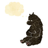 schwarzer Bär der netten Karikatur mit Gedankenblase Stockfoto
