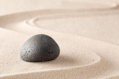 Schwarzer Basaltstein auf Sand des sandigen Strandes mit Linie Muster lizenzfreies stockbild