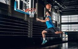 Schwarzer Basketball-Spieler in der Aktion in einem Basketballplatz stockbild