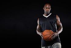 Schwarzer Basketball-Spieler mit Ball Stockfoto
