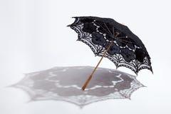 Schwarzer Battenburg Spitzesonnenschirm und -schatten Stockfotos