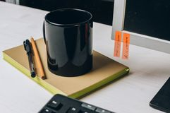 Schwarzer Becher auf einem Notizbuch nahe bei einem Computer lizenzfreies stockfoto