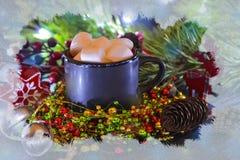 Schwarzer Becher gefüllt mit Eibisch auf dem Hintergrund von Weihnachtsdekorationen und -Fichtenzweigen Der Effekt des gefrorenen stockfotos