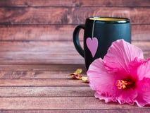 Schwarzer Becher Tee mit einem rosa Herzen auf einem Schnur Rosahibiscus blühen auf dunklem hölzernem Hintergrund Kopienraum Stockfoto