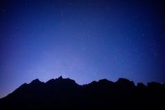 Schwarzer Berg mit blauem Himmel und vollen Sternen stockbilder