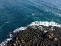 Schwarzer Berg und blaues Meer Lizenzfreies Stockfoto