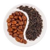 Schwarzer Blatttee gegen Kaffeebohnen in Yin Yang Stockfoto