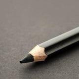 Schwarzer Bleistift auf dunkler Oberfläche lizenzfreie stockbilder