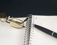 Schwarzer Bleistift auf geöffnetem Weißbuchanmerkungsbuch Lizenzfreie Stockfotos