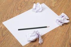 Schwarzer Bleistift auf klarem Weißbuch mit Krümelpapierbällen auf wo Stockfotos