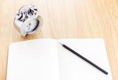 Schwarzer Bleistift auf offenem Notizbuch des freien Raumes mit silbernem Wecker besi Stockbild