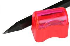 Schwarzer Bleistift und roter Bleistiftspitzer Lizenzfreies Stockfoto