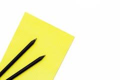 Schwarzer Bleistift zwei und ein gelber Notizblock auf einem weißen Hintergrund Minimaler Konzeptarbeitsplatz im Büro Stockfotografie