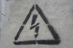 Schwarzer Blitz in einem Dreieck auf einer Betondecke Lizenzfreie Stockfotos