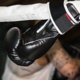 Schwarzer Boxhandschuh gebunden an Ring Ropes Stockbilder