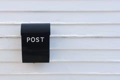 Schwarzer Briefkasten auf weißer hölzerner Wand des Hauses Stockfotos