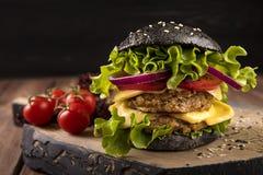 Schwarzer Burger des strengen Vegetariers mit zwei Kichererbsenkoteletts, -tomaten, -käse, -zwiebel und -salat auf Holztisch, dun Stockfoto