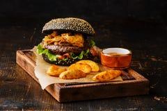 Schwarzer Burger mit Fleisch, Zwiebelringfischrogen und Kartoffelkeilen Lizenzfreie Stockfotos