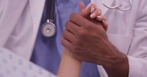 Schwarzer Doktor, der die Hand des Patienten hält Lizenzfreies Stockfoto