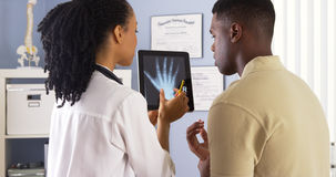 Schwarzer Doktor, der Strahl der Hand x mit Patienten auf Tablette teilt stockbild