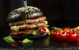 Schwarzer doppelter Hamburger gemacht vom Rindfleisch, mit Jalapenopfeffer Stockbilder