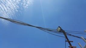 Schwarzer Draht und Scheinwerferlicht mit Hintergrund des blauen Himmels Stockfotos