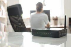Schwarzer drahtloser Router auf weißer reflektierender Oberfläche Stockbild