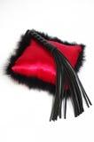 Schwarzer Fetisch, der Peitsche und auf rotem Kissen prügelt Stockfotos