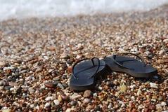 Schwarzer Flip Flops auf dem Strand, mit Meer auf Hintergrund Feiertagskonzept Sommer ferien stockbild