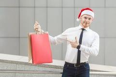 Schwarzer Freitag im Winter Glückroter Hauptgeschäftsmann in Sankt-Hut, Einkaufstaschen auf Händen halten und zeigen Finger und d Lizenzfreies Stockbild