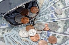 Schwarzer Geldbeutel mit Cents auf dem Hintergrund von Hundertdollar-Rechnungen Stockbild