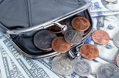 Schwarzer Geldbeutel mit Cents auf dem Hintergrund von Hundertdollar-Rechnungen Lizenzfreie Stockbilder