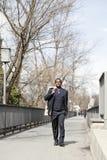 Schwarzer Geschäftsmann, der auf Straße geht Lizenzfreie Stockfotos