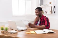 Schwarzer Geschäftsmann im zufälligen Büro, Arbeit mit Laptop und Tablette Stockbilder
