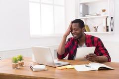 Schwarzer Geschäftsmann im zufälligen Büro, bearbeiten beide auf Laptop und Tablette Stockbilder