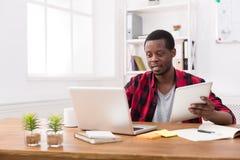 Schwarzer Geschäftsmann im zufälligen Büro, bearbeiten beide auf Laptop und Tablette Stockfotografie