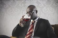 Schwarzer Geschäftsmann-trinkender Wein stockfoto