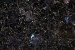 Schwarzer Granit mit Höhepunkten des Nachtlebens Stockfoto