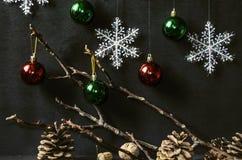Schwarzer hölzerner Hintergrund mit Schneeflocken, farbige Bälle auf einer trockenen Niederlassung Lizenzfreie Stockfotografie