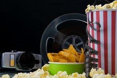 Schwarzer Hintergrund, alte Videokamera, Popcorn, Film, an der Stange auf dem Tisch lizenzfreie stockfotos