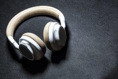 Schwarzer Hintergrund Große Kopfhörer für das Hören von Musik Weiße und beige Farbe haut Moderne Technologien Transportables Gerä lizenzfreies stockfoto