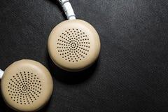 Schwarzer Hintergrund Große Kopfhörer für das Hören von Musik Weiße und beige Farbe haut Moderne Technologien Transportables Gerä lizenzfreie stockbilder