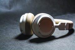 Schwarzer Hintergrund Große Kopfhörer für das Hören von Musik Weiße und beige Farbe haut Moderne Technologien Transportables Gerä stockfotografie